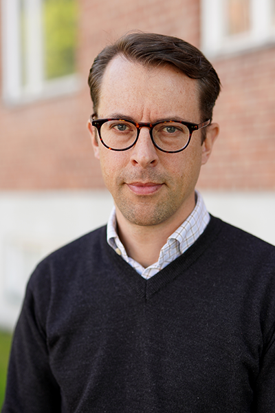 Man with dark hair and glasses looks into camera. Portrait photo.